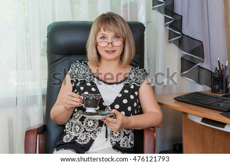 Smiling adult woman with cup coffee or tea at desk in her apartment. Break during work on computer