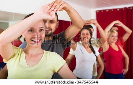 Smiling adults dancing a bachata together in dance studio