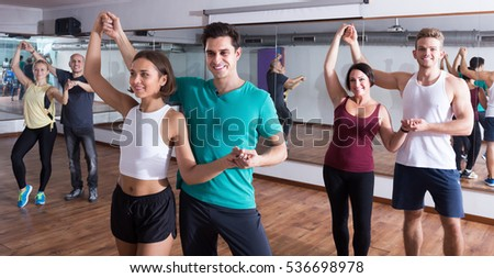 Smiling adults dancing bachata together in dance class