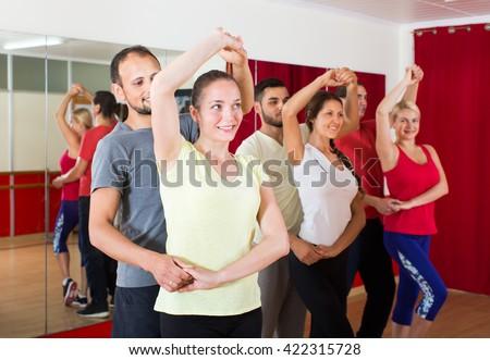 Smiling adults dancing the bachata together in the dance studio