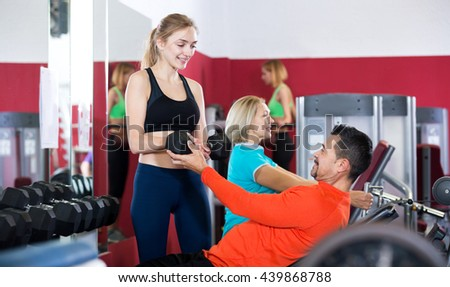 Smiling adults of different age having strength training in sport club