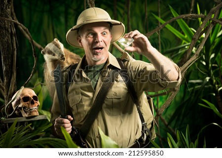 Smiling adventurer finding a huge diamond in the jungle with explorer equipment. - stock photo