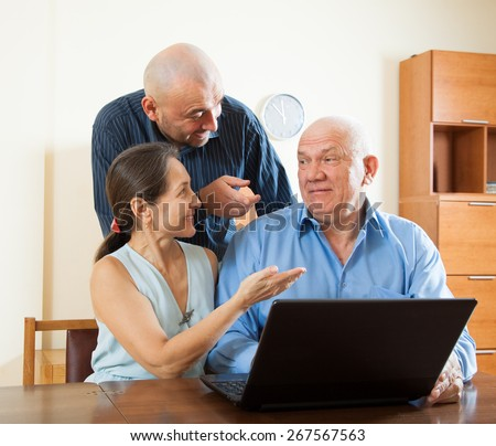 Smiling advisor  standing near mature couple with laptop
