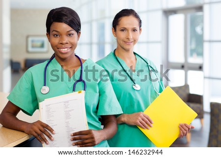 Smiling African American and caucasian nurse at hospital work station lit brightly with carts and wearing stethoscopes. - stock photo