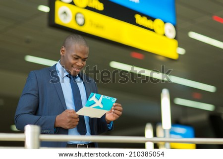 smiling african american businessman checking his flight ticket at airport - stock photo