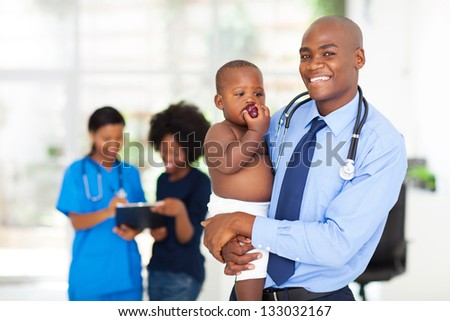 smiling african american doctor holding baby with mother and nurse on background