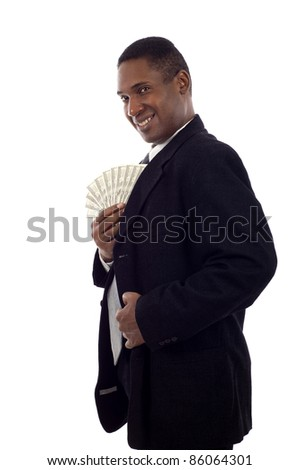Smiling African American man putting lots of money in his pocket isolated white background