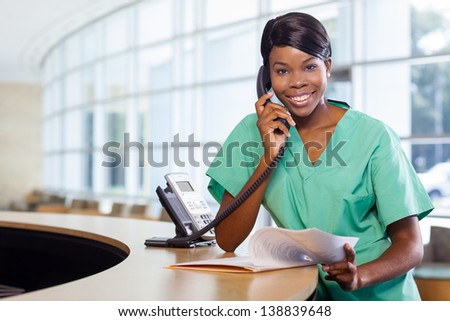 Smiling African American nurse at hospital work station lit brightly with phone and stethoscope. - stock photo