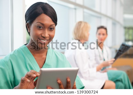 Smiling African- American nurse holding tablet with . a Caucasian and Hispanic doctor in background, looking at scan in hospital - stock photo