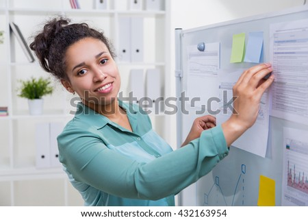 Smiling african american woman in office next to whiteboard with sticker memos and printed business charts - stock photo