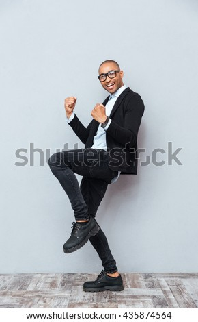 Smiling african american young man standing and celebrating success - stock photo