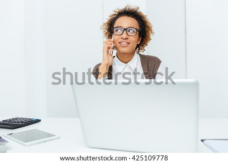 Smiling african american young woman accountant working with laptop and talking on cell phone on workplace - stock photo