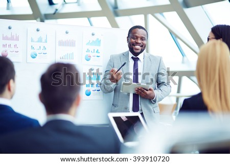 Smiling African businessman explaining project to his colleagues
