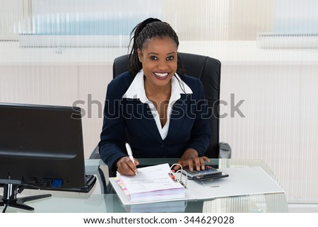 Smiling African Businesswoman Calculating Bills At Office Desk - stock photo