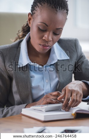 Smiling african businesswoman in formalwear sitting at workplace and planning - stock photo