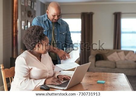 Smiling African couple paying bills and doing their online banking with a laptop at their kitchen table at home