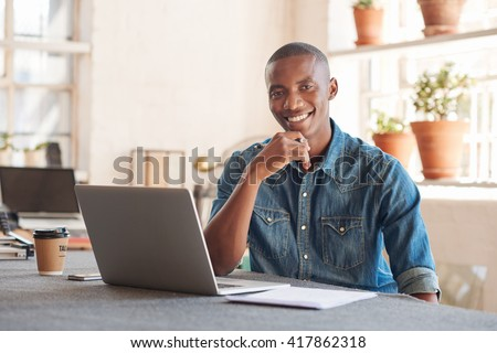 Smiling African designer with laptop in beautifully lit studio - stock photo