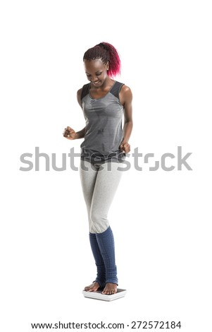 Smiling african fitness young woman standing on scales - stock photo