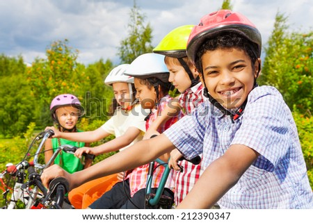 Smiling African guy in helmet with friends behind