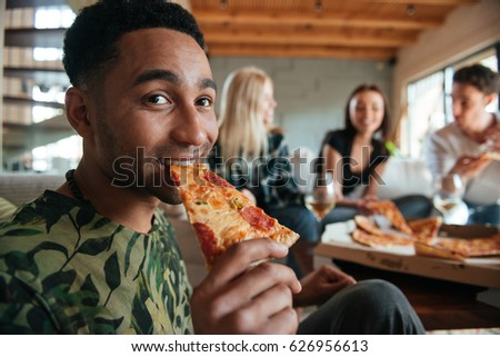 Smiling African man eating pizza surrounded by friends in the house