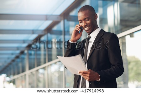 Smiling African man using his phone and looking at paperwork - stock photo