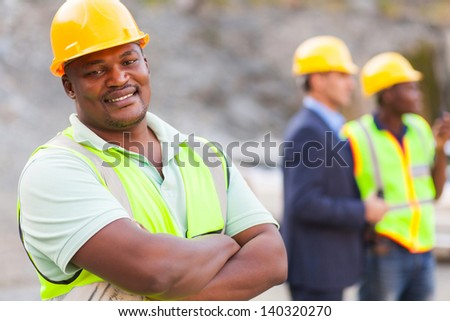 smiling african mine worker at mining site with colleagues - stock photo