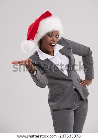 Smiling african Santa Girl presenting your product, lots of copyspace - stock photo