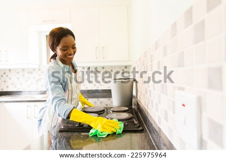 smiling african woman cleaning the stove - stock photo