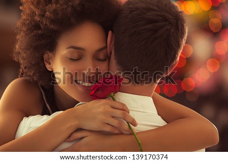 Smiling African woman hugging her boyfriend and holding the rose she got for Valentine's Day. - stock photo