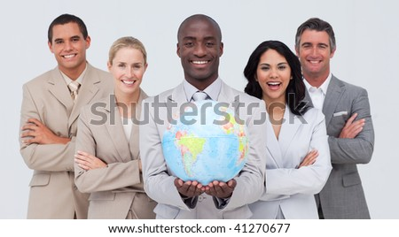 Smiling Afro-American businessman holding a terrestrial globe with his team - stock photo