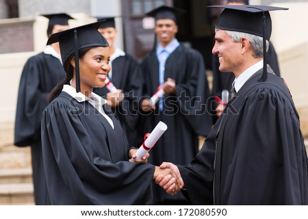 smiling afro american female graduate handshaking with dean - stock photo