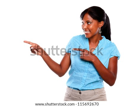 Smiling afro-american woman pointing and looking to her right against white background - copyspace - stock photo