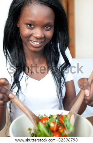 Smiling Afro-american woman preparing a salad at home - stock photo