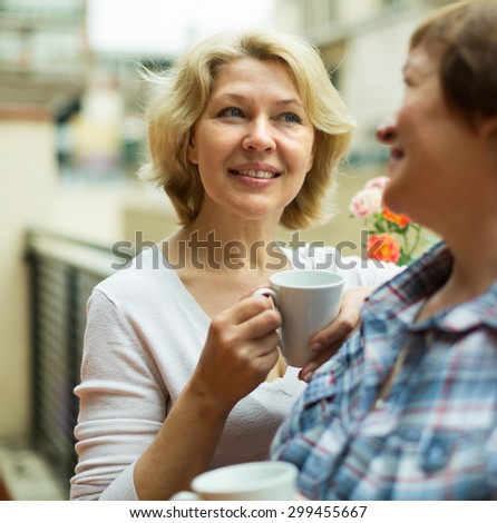 Smiling aged female friends staying on balcony with cup of coffee in hands