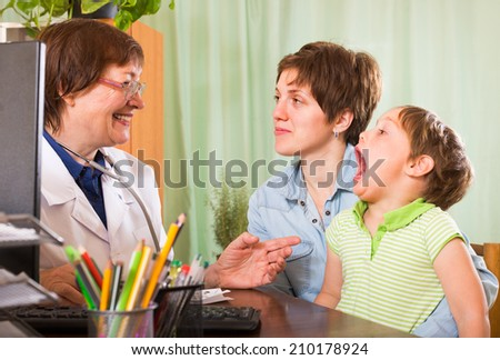 Smiling aged female pediatrician doctor examining child at clinic   - stock photo