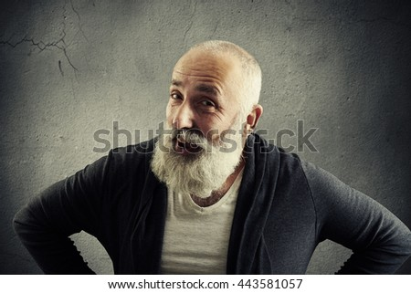 Smiling aged man with white beard in stylish casual clothes is posing at the camera with hands on hips against grey concrete wall