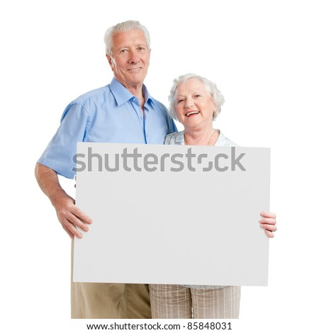 Smiling aged retired couple holding together a white board isolated on white background