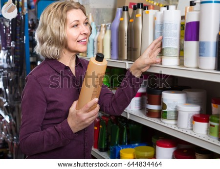 Smiling aged woman selecting  shampoo in beauty store