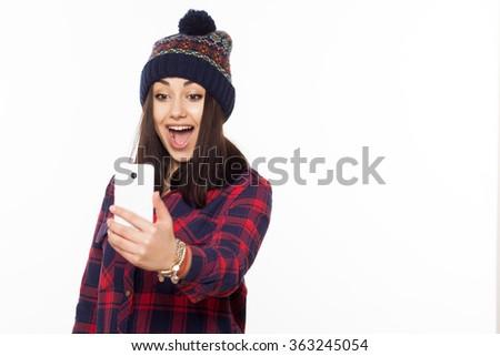 Smiling amazed young hipster girl making selfie photo isolated on white background - stock photo