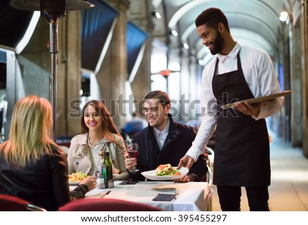 smiling american afro waiter taking table order and smiling in winter evening