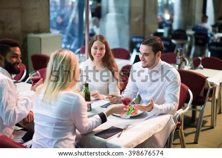smiling american middle class people enjoying food in cafe terrace - stock photo