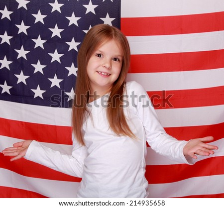 Smiling American schoolgirl standing against the background of the American flag
