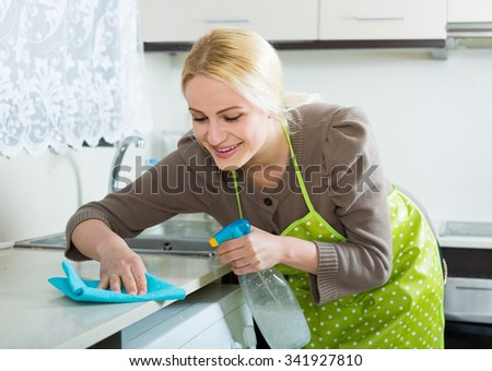 Smiling american  young housewife cleaning furniture in kitchen   - stock photo