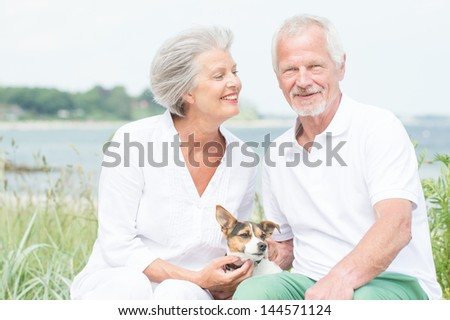 Smiling and actice senior couple with dog - stock photo