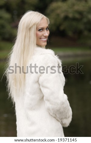 smiling and beautiful girl with long hair wearing a white fur