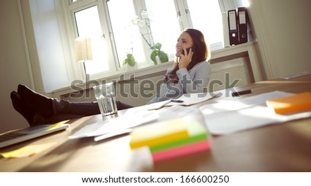 Smiling and beautiful young businesswoman sitting at her desk with legs on table talking on mobile phone smiling. Caucasian young female entrepreneur working in home office. - stock photo