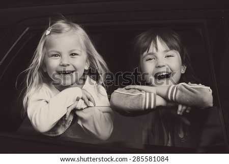 smiling and charming children look through the glass in the car - stock photo