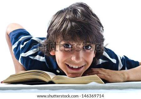 Smiling and cheerful boy reading and studying school book - stock photo