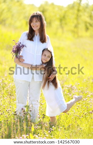 Smiling and cheerful mother and daughter with long dark hair walking and laughing at summer green grass outdoors - stock photo