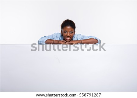 smiling and cheerfull black woman leaning on an white empty board showing confidence and joy